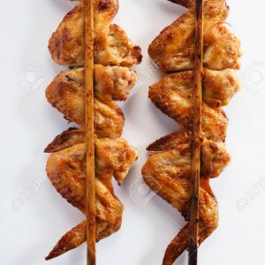 roasted chicken wings in wooden skewer on white background, top view